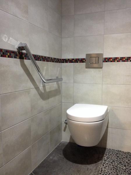 WC bati suspendu avec abattant frein de chute, barre d'appui pour personnes à mobilité réduite. Visible dans notre show-room à la Riche